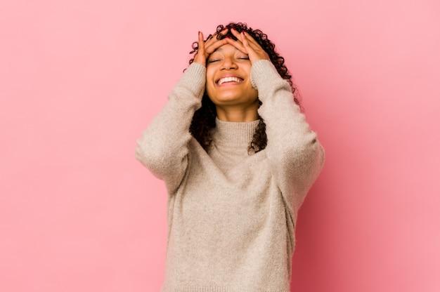 Jonge afrikaanse amerikaanse afro geïsoleerde vrouw lacht vreugdevol handen op het hoofd te houden. geluk concept.