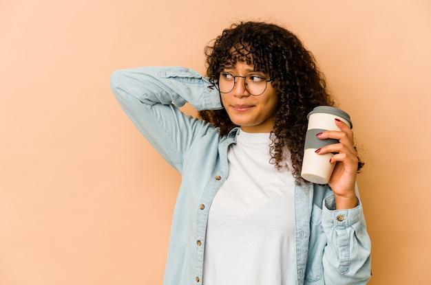 Jonge afrikaanse amerikaanse afrovrouw die een afhaalkoffie houdt die achterkant van het hoofd raakt, denkt en een keus maakt.
