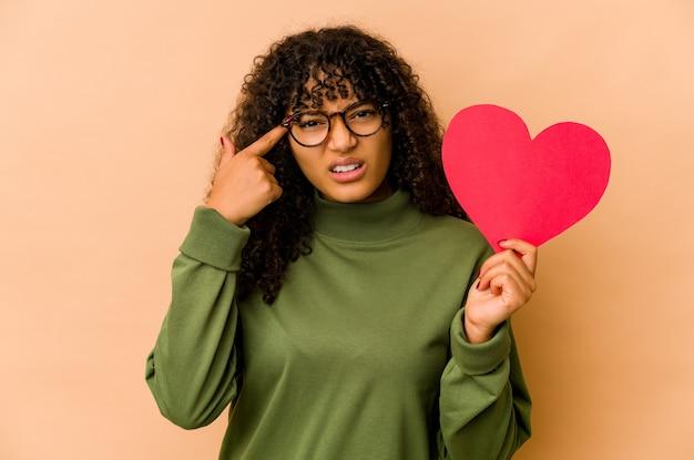 Jonge afrikaanse amerikaanse afrovrouw die een hart van de valentijnskaartendag houdt dat een teleurstellinggebaar met wijsvinger toont.