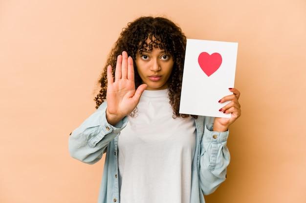 Jonge afrikaanse amerikaanse afrovrouw die een kaart van de valentijnskaartendag houdt die zich met uitgestrekte hand bevindt die stopbord toont, dat u verhindert.