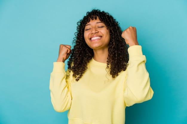 Jonge afrikaanse amerikaanse afrovrouw die een overwinning, hartstocht en enthousiasme, gelukkige uitdrukking viert.