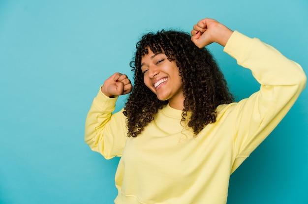 Jonge afrikaanse amerikaanse afrovrouw die een speciale dag viert, springt en heft wapens op met energie.