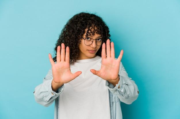 Jonge afrikaanse amerikaanse afrovrouw geïsoleerde status met uitgestrekte hand die stopbord toont, dat u verhindert.