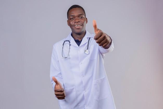 Jonge afrikaanse amerikaanse arts die witte laag met stethoscoop draagt die zelfverzekerd glimlacht toont duimen met beide handen