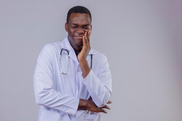 Jonge afrikaanse amerikaanse arts die witte laag met stethoscoop draagt die zijn wang raakt die aan pijn lijden met kiespijn