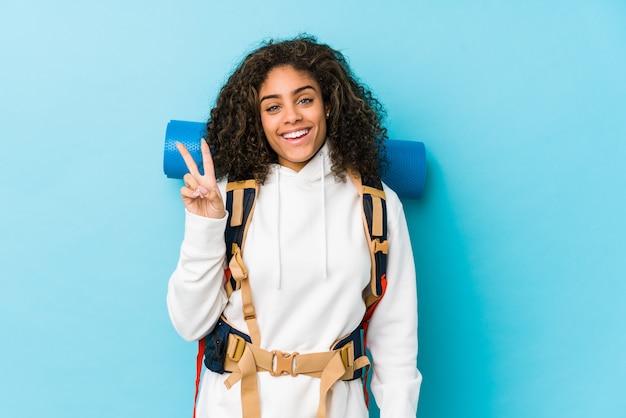 Jonge afrikaanse amerikaanse backpackervrouw blij en onbezorgd tonend een vredessymbool met vingers.