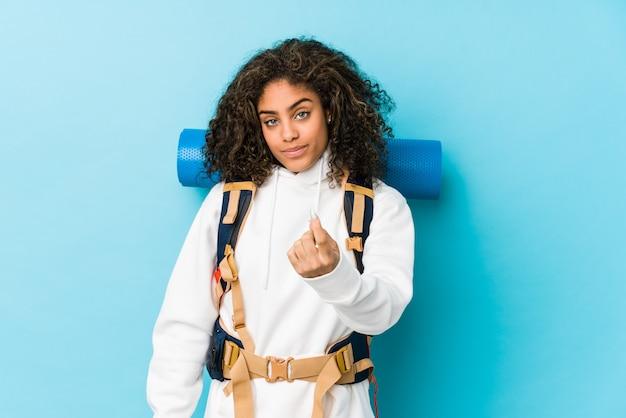 Jonge afrikaanse amerikaanse backpackervrouw die met vinger op u richten alsof uitnodigend dichterbij kom.