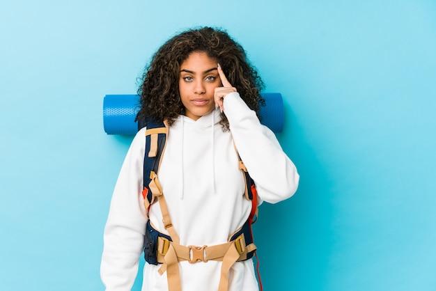 Jonge afrikaanse amerikaanse backpackervrouw die tempel met vinger richten