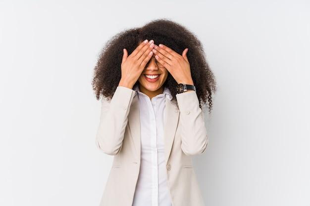 Jonge afrikaanse amerikaanse bedrijfsvrouw behandelt ogen met handen, glimlacht in het algemeen wachtend op een verrassing.
