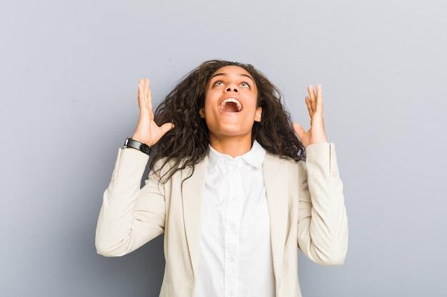 Jonge afrikaanse amerikaanse bedrijfsvrouw die aan de hemel gilt, gefrustreerd omhoog kijkt.