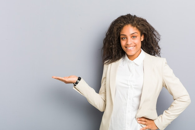 Jonge afrikaanse amerikaanse bedrijfsvrouw die een exemplaarruimte op een palm toont en een andere hand op taille houdt.