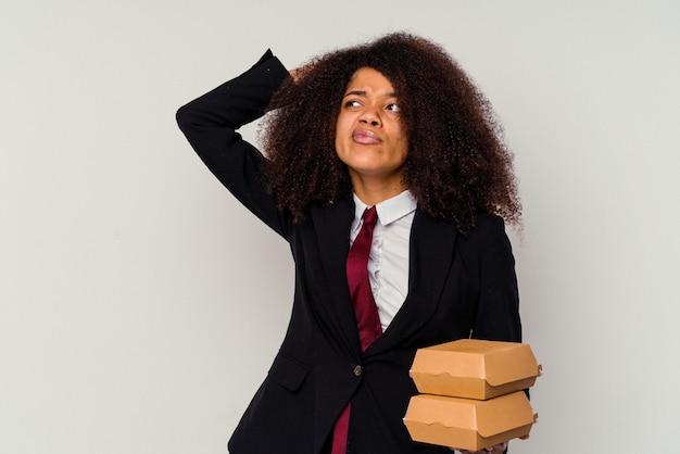 Jonge afrikaanse amerikaanse bedrijfsvrouw die een hamburger houdt die op witte achtergrond wordt geïsoleerd die achterkant van het hoofd raakt, denkt en een keus maakt.