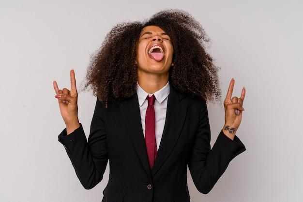 Jonge afrikaanse amerikaanse bedrijfsvrouw die een kostuum draagt dat op wit wordt geïsoleerd dat rotsgebaar met vingers toont