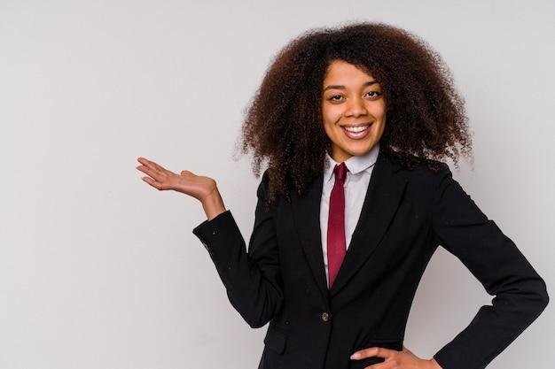 Jonge afrikaanse amerikaanse bedrijfsvrouw die een kostuum draagt dat op witte achtergrond wordt geïsoleerd die een exemplaarruimte op een palm toont en een andere hand op taille houdt.