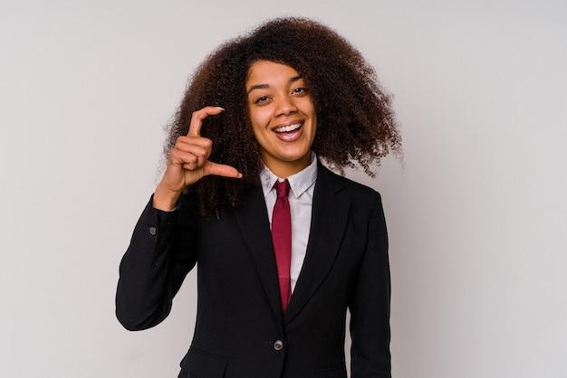 Jonge afrikaanse amerikaanse bedrijfsvrouw die een kostuum draagt dat op witte achtergrond wordt geïsoleerd die iets kleins met wijsvingers houdt, glimlachend en zelfverzekerd.
