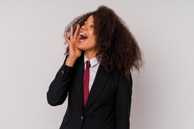 Jonge afrikaanse amerikaanse bedrijfsvrouw die een kostuum draagt dat op witte achtergrond wordt geïsoleerd die schreeuwen en palm dichtbij geopende mond houdt.