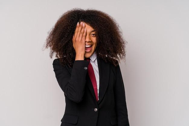 Jonge afrikaanse amerikaanse bedrijfsvrouw die een kostuum draagt dat op witte muur wordt geïsoleerd die pret heeft die de helft van het gezicht bedekt met palm.