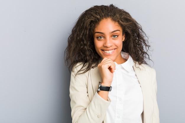 Jonge afrikaanse amerikaanse bedrijfsvrouw die gelukkige en zekere, uching kin met hand glimlacht.