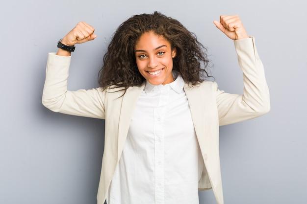 Jonge afrikaanse amerikaanse bedrijfsvrouw die krachtgebaar met wapens, symbool van vrouwelijke macht toont
