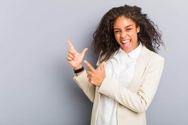 Jonge afrikaanse amerikaanse bedrijfsvrouw die met wijsvingers aan een exemplaarruimte richt, opwinding en wens uitdrukt.