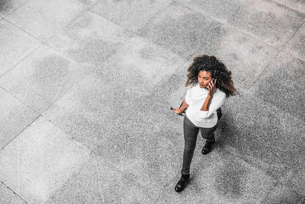Jonge afrikaanse amerikaanse bedrijfsvrouw die op de telefoon op haar manier aan werkplaats spreekt.