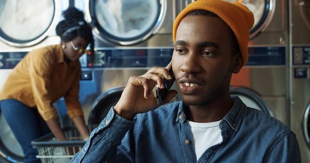 Jonge afrikaanse amerikaanse blije knappe kerel in gele hoed die op mobiele telefoon spreekt en in wasserieruimte glimlacht. gelukkig man spreken op mobiel in washuis. smartphone-gesprek.