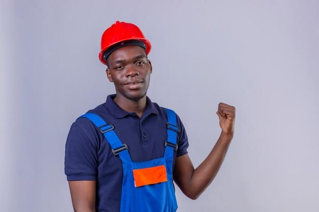Jonge afrikaanse amerikaanse bouwersmens die bouwuniform en veiligheidshelm draagt die naar achteren wijzen met hand en duim omhoog glimlachend zelfverzekerd staan