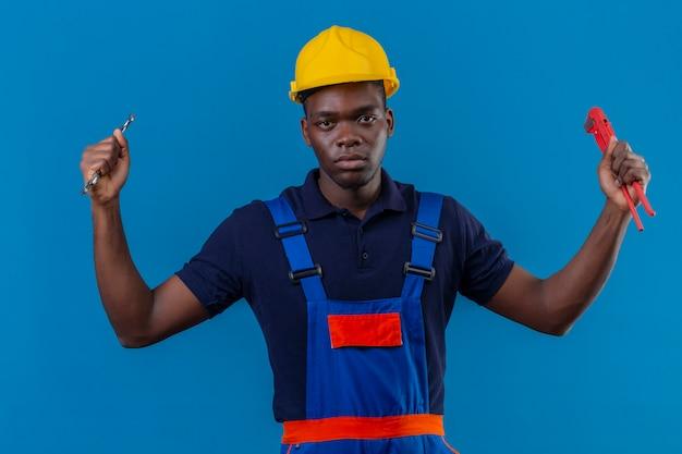 Jonge afrikaanse amerikaanse bouwersmens die bouwuniform en veiligheidshelm draagt die regelbare moersleutels in opgeheven hand met agressieve boze uitdrukking staande houdt