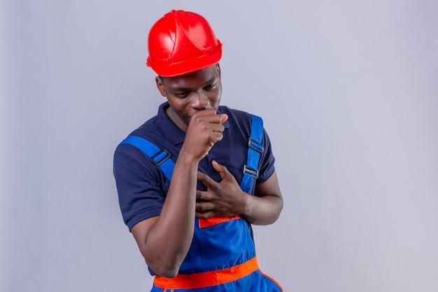 Jonge afrikaanse amerikaanse bouwersmens die bouwuniform en veiligheidshelm draagt, zich onwel voelt en hoestend status op geïsoleerd wit