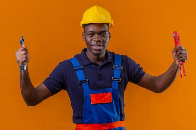 Jonge afrikaanse amerikaanse bouwersmens die bouwuniform en veiligheidshelm dragen die regelbare moersleutels in opgeheven handen houden met blij gezicht dat zich op oranje bevindt