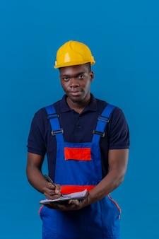 Jonge afrikaanse amerikaanse bouwersmens die bouwuniform en veiligheidshelm dragen met klembord en pen die aantekeningen gaan maken met vriendelijke glimlach die zich op blauw bevindt