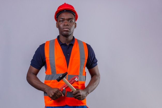 Jonge afrikaanse amerikaanse bouwersmens die bouwvest en veiligheidshelm dragen die regelbare moersleutel en hamer in dwarsvorm met ernstig gezicht status houden