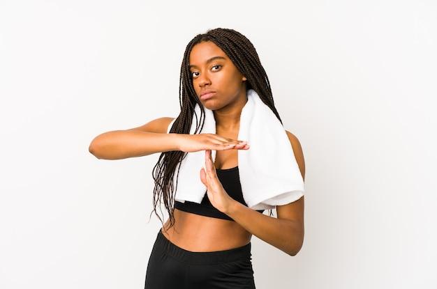 Jonge afrikaanse amerikaanse geïsoleerde sportvrouw toont een time-outgebaar.