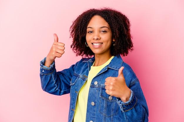 Jonge afrikaanse amerikaanse gemengde rasvrouw die beide duimen opheft, glimlachend en zelfverzekerd.