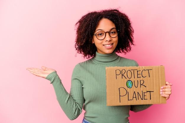 Jonge afrikaanse amerikaanse gemengde rasvrouw die beschermt onze planeetkarton houdt dat een exemplaarruimte op een palm toont en een andere hand op taille houdt.