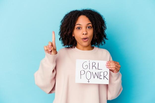 Jonge afrikaanse amerikaanse gemengde rasvrouw die een concept van de meisjesmacht houdt dat één of ander geweldig idee, concept van creativiteit heeft.