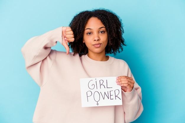 Jonge afrikaanse amerikaanse gemengde rasvrouw die een concept van de meisjesmacht houdt die een afkeergebaar, duimen naar beneden toont. meningsverschil concept.