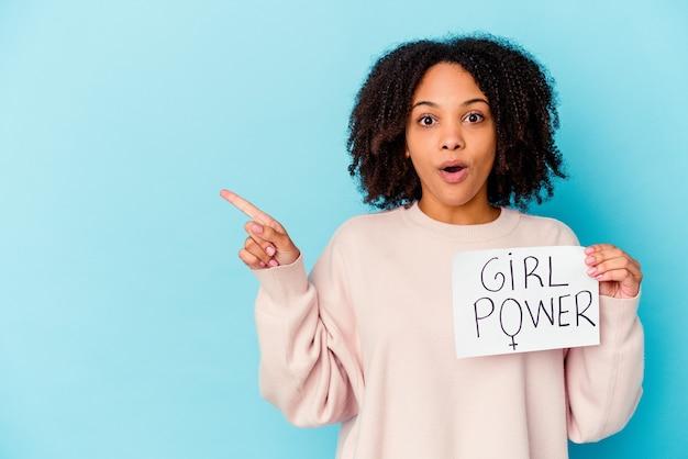 Jonge afrikaanse amerikaanse gemengde rasvrouw die een concept van de meisjesmacht houdt die naar de kant richt