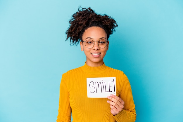 Jonge afrikaanse amerikaanse gemengde rasvrouw die een gelukkig, glimlachend en vrolijk glimlachconcept houden.