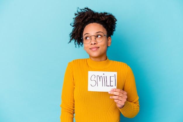Jonge afrikaanse amerikaanse gemengde rasvrouw die een glimlachconcept houden die van het bereiken van doelstellingen en doeleinden dromen