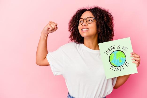 Jonge afrikaanse amerikaanse gemengde rasvrouw die een het conceptenkarton van de wereldbescherming houden vuist opheft na een overwinning, winnaarconcept.