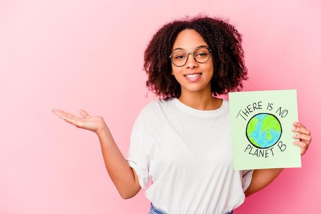 Jonge afrikaanse amerikaanse gemengde rasvrouw die een het conceptenkarton van de wereldbescherming houdt dat een exemplaarruimte op een palm toont en een andere hand op taille houdt.