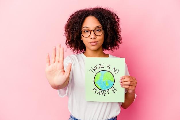 Jonge afrikaanse amerikaanse gemengde rasvrouw die een het conceptenkarton van de wereldbescherming houdt dat zich met uitgestrekte hand bevindt die stopbord toont, dat u verhindert.