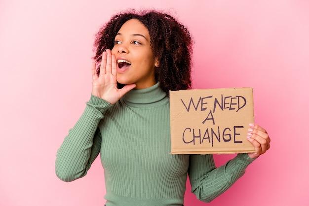 Jonge afrikaanse amerikaanse gemengde rasvrouw die een inspirerend berichtkarton houdt dat schreeuwt en palm dichtbij geopende mond houdt.