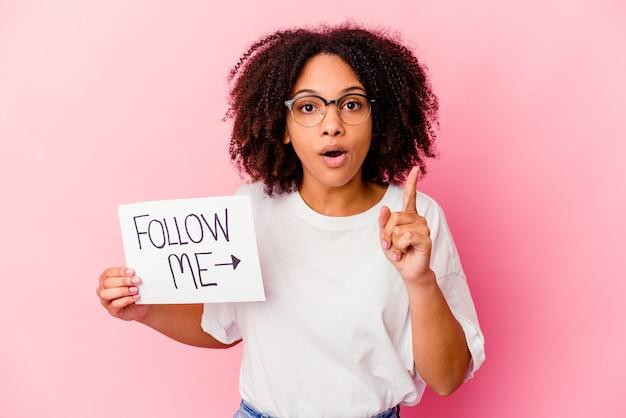 Jonge afrikaanse amerikaanse gemengde rasvrouw die een volgen-mij-concept houden met een idee, inspiratieconcept.