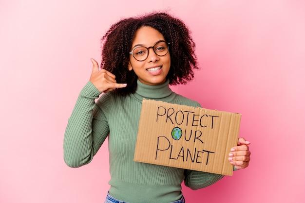 Jonge afrikaanse amerikaanse gemengde rasvrouw die houden beschermt ons planeetkarton dat een mobiel telefoongesprekgebaar met vingers toont.
