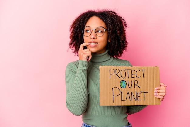 Jonge afrikaanse amerikaanse gemengde rasvrouw die houden beschermt onze planeetkarton ontspannen denkend aan iets dat een exemplaarruimte bekijkt.