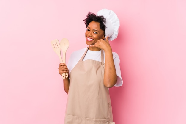 Jonge afrikaanse amerikaanse kokvrouw die een gsm-gebaar met vingers toont.