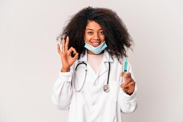 Jonge afrikaanse amerikaanse krullende artsenvrouw die een spuit vrolijk en zelfverzekerd houdt die ok gebaar toont.