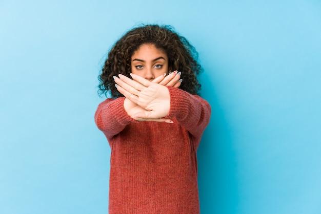 Jonge afrikaanse amerikaanse krullende haarvrouw die een ontkenningsgebaar doet